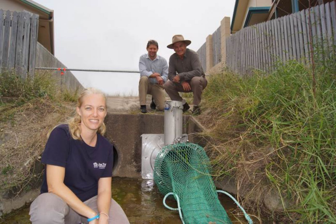 Townsville Local Marine Advisory Committee members fit gross pollutant traps at storm water drain outlets to prevent rubbish entering the ocean